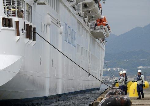 豪華客船の着岸、ロープを張るスタッフ