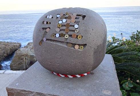 鵜戸神宮で亀石の枡形に運玉を投げ入れる「運玉投げ」