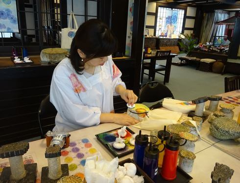 沖縄で「サンゴ染め体験」割烹着でトライ